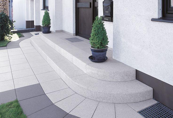 Passend zum Charakter des Hauses fügt sich der Eingangsbereich durch Farbe, Form und Schwingung an. Durch seinen Zuweg, der mit einem Mix von dunklen und hellen Tönen einen schönen Rahmen bildet. Durch die radiale Form der Stufen, die die Architektur des Hauses aufnimmt.
