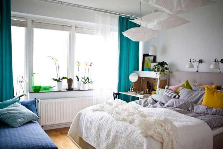 Blick auf ein Schlafzimmer mit Stoffen in neutralen und bunten Farben. Blaue und weiße Elemente unterstreichen das Meeresthema.