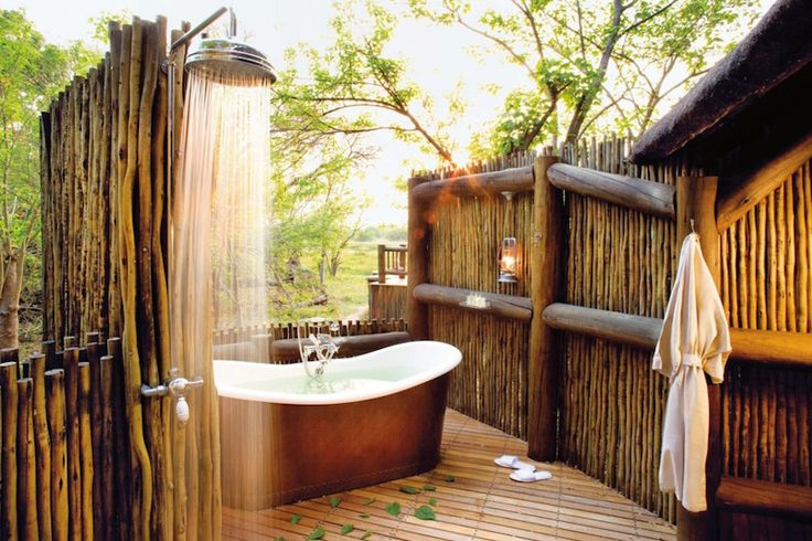 Adorable rustic and tropical outdoor bathroom with brown freestanding bathtub, wooden floor, and rustic fence chrome faucet. 10 Stunning Tropical Bathroom Décor Ideas to Inspire You ➤To see more Luxury Bathroom ideas visit us at www.luxurybathrooms.eu #luxurybathrooms #homedecorideas #bathroomideas @BathroomsLuxury