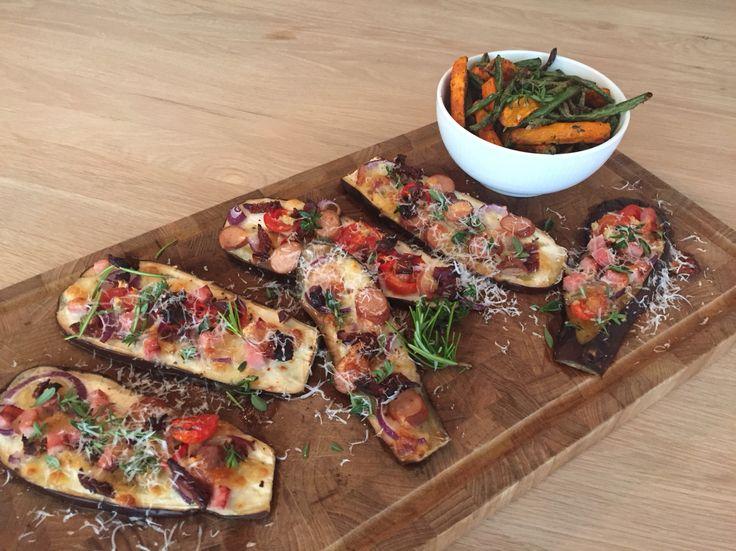 """Aubergine """"pizza"""" med kyllingpølser, skinke, løg, mozzarella, tomat, soltørret tomat, friske krydderurter og bønne/gulerodsfritter."""
