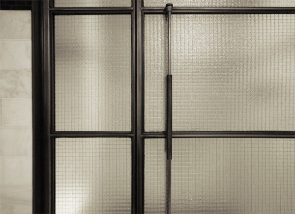 Detail of a custom shower enclosure in blackened stainless steel by Face Design + Fabrication