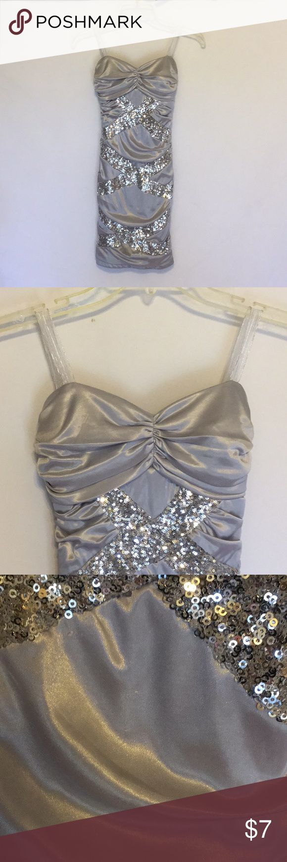 """Silver Sequin Dress Perfect for a holiday party. Ribbon was added for straps but can be easily removed. Back zipper. Form fitting. Does run small for a 5.  There are a few small snags on the front of the dress, otherwise In good condition.  Approximate measurements: Taken while the garment is laying flat and unstretched; appropriate measurements can be doubled for total circumference. Length:  28"""" Underarm to underarm:  11.5"""" Waist seam to seam:  9.5"""" Made of:  polyester with nylon lining…"""