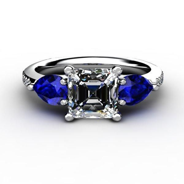 Beautiful center asscher cut diamond engagement ring with flanking blue pear cut sapphires, accented by small diamonds on each side.
