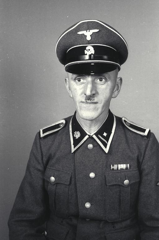 Mauthausen concentration camp: An SS-Scharführer wearing a gray-green field uniform. The silver-gray braid on the collar was used by all SS non-commissioned officers. The face is perfect for the barbaric role.
