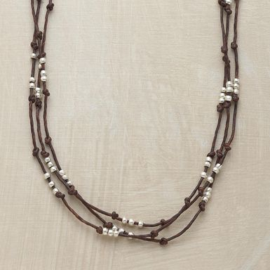 Silver beads bob between knots on strands of waxed brown linen.  From Sundance.