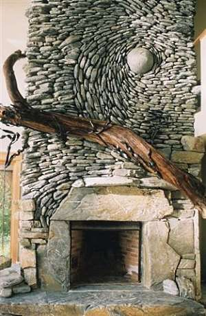 Spiral river stone fireplace by Andreas Kunert of Ancient Art of Stone in Victoria, British Columbia, Canada.