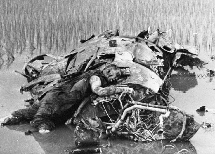 An American pilot lies dead on the wreckage of his plane in North Vietnam…
