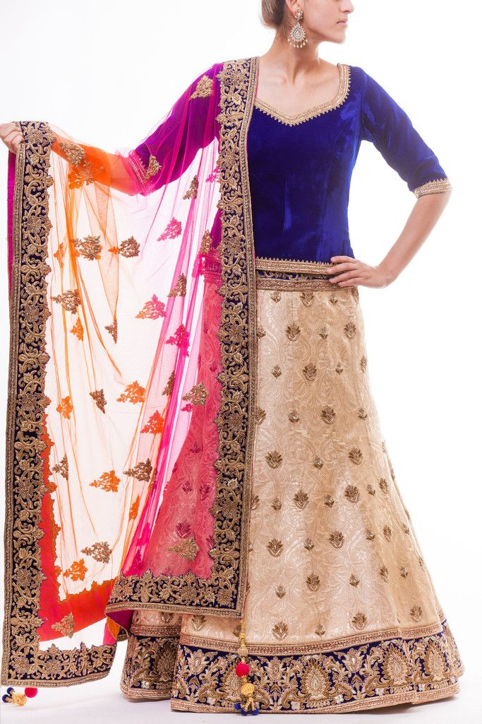 Traditional khinkhab silk gold lehenga paired with Blue Velvet Blouse paired with orange-hot pink ombre dupatta with Blue Border.