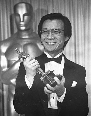 """Cambodian refugee Dr. Haing S. Ngor, winner of the Best Supporting Actor category for his role in """"The Killing Fields"""",  holds high his Oscar backstage at the 57th annual Academy Awards presentations Monday, March 26, 1985.  (AP Photo) / SF"""