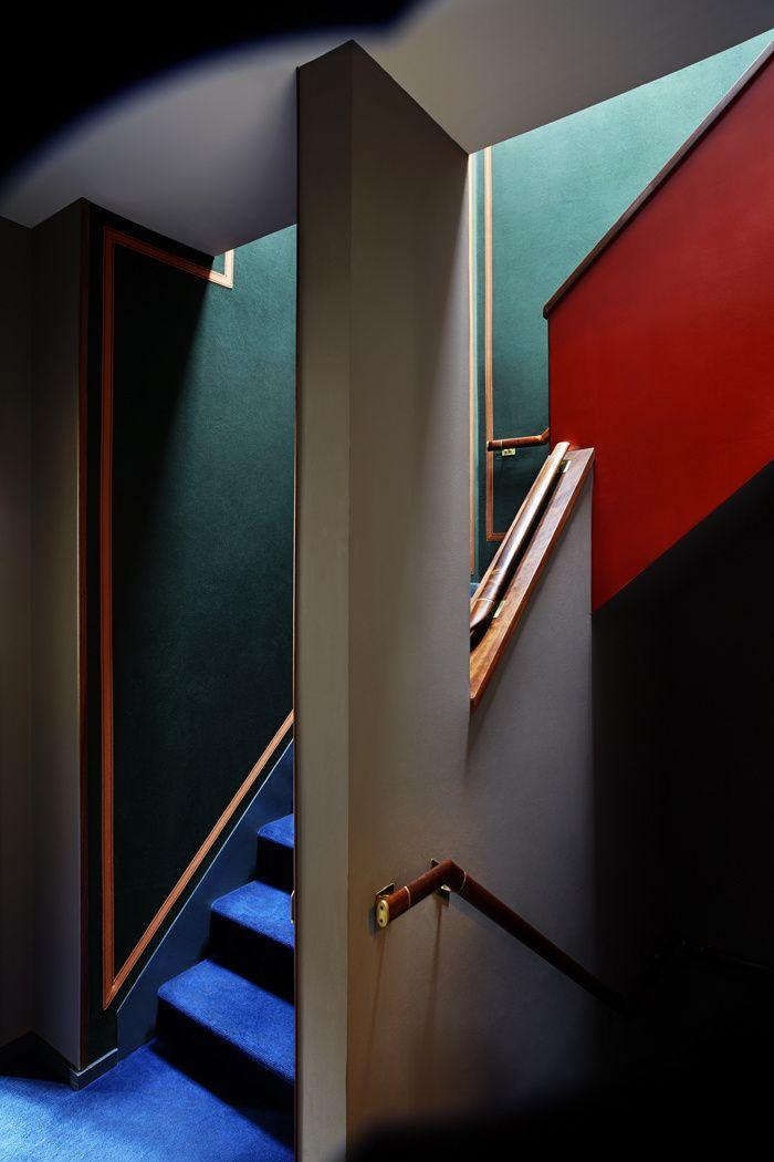 Tout l'esprit de la maison semble converger dans la cage d'escalier, où les murs bleu canard et brique rencontrent une moquette bleu Klein. © Christopher Sturman