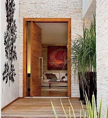 No hall de entrada, a porta pivotante e o piso são de madeiras de demolição. Na parede revestimento de canjiquinha