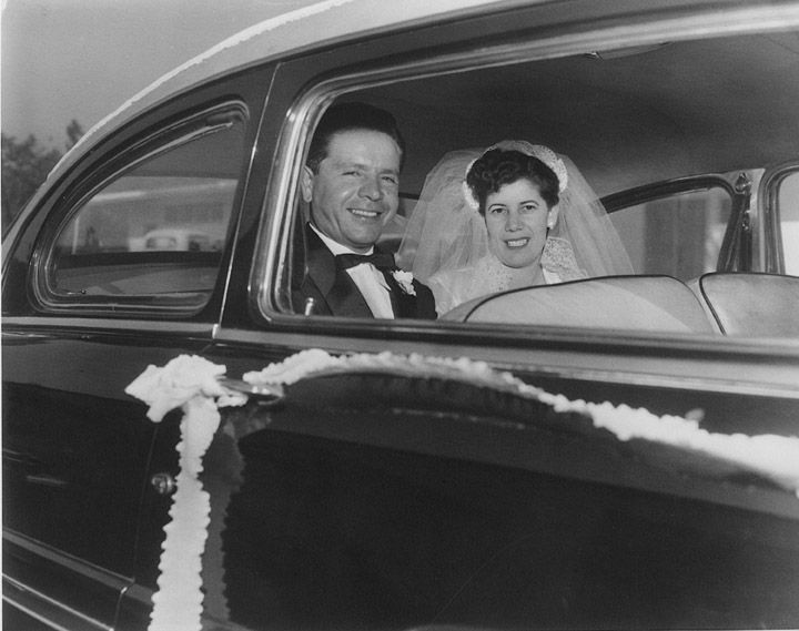 Groom Richard Martinez and bride Kate San Roman Martinez, in back seats of decorated automobile, after their wedding at Holy Family Catholic Church, Orange, California, November 28, 1953.