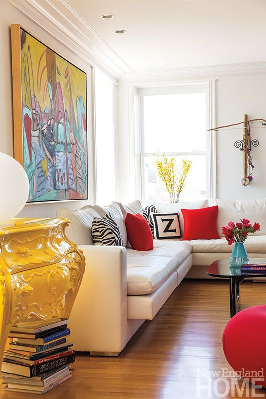 An ornate lacquered bombé chest in a bright, colorful family room anchors a custom leather sofa. Photo by Keller + Keller