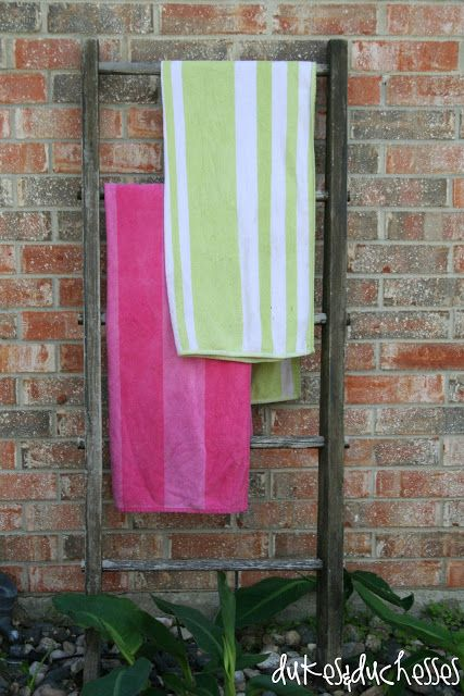 a vintage ladder repurposed into a pool towel drying rack
