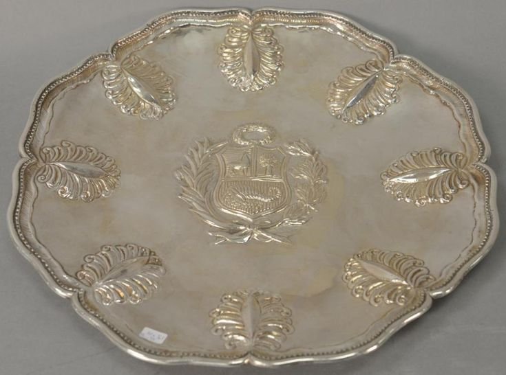 South American sterling silver sideboard dish, probably Peru, center chased with an armorial emblem within a foliate wreath,  - Price Estimate: $350 - $550