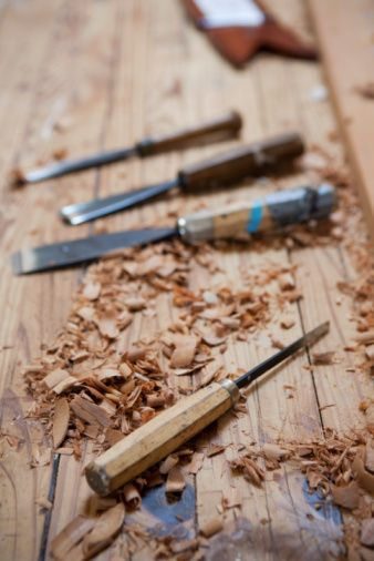 Several wood chisels on a wooden work bench with wood shavings around them. @RTpinterests