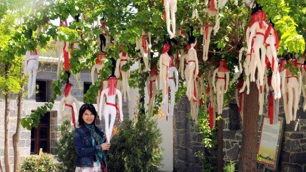 'Çocuk gelinlere' dikkat çekmek için kilisedeki ağaca bezden yaptığı çocuk gelinleri astı