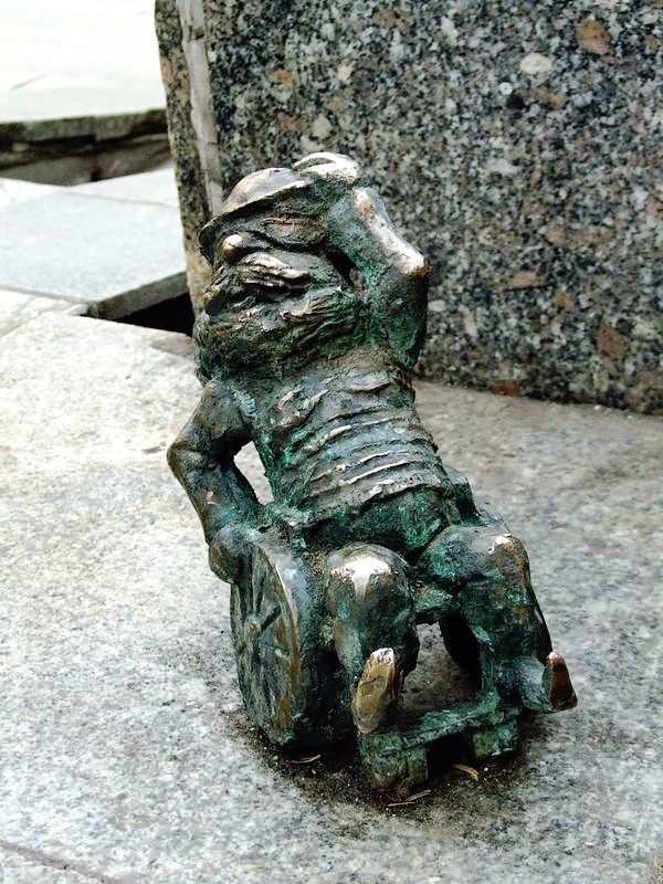 A small statue of a gnome in a wheelchair, one of 70 such statues scattered around Wroclaw, Poland, in homage to the Orange Alternative anti-Communist movement of the 1980s.