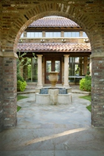 mediterranean exterior w/ courtyard and glass enclosed gallery entry / Norris Architecture
