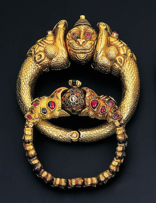 India | A pair of 'Garuda Head' bracelets | gold with diamond, ruby and emerald details | ca. late 19th century, South India | The first designed as a flexible garuda head bracelet with diamond, ruby and emerald detail to the larger gem-set garuda head terminals supporting an emerald-set sphere; the second hinged bangle with similar garuda head terminals supporting a stylised asura head with ruby detail