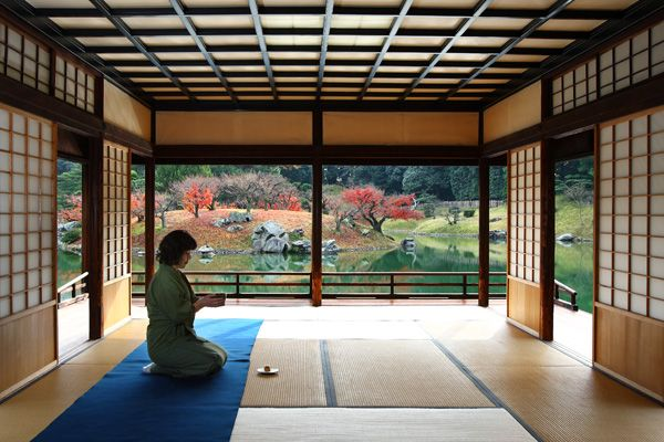 woman prepares tea at a traditional japanese tea house inside
