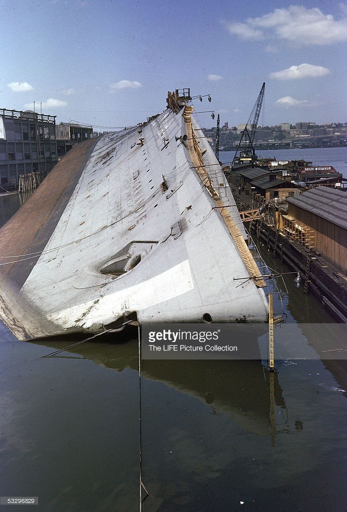 View of the French luxury ocean liner SS Normandie as it lies on its side and half-submerged in dock, New York, New York, June 1942. The ship had been seized by the US government after France's surrender to German in World War II, renamed the USS Lafayette, and was in the process of being refitted as an American troop transport when an accidental fire broke out, seriously damaging the ship.