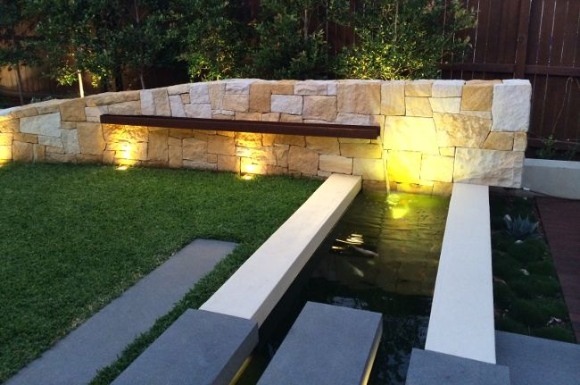 Sandstone water feature with custom corten steel water trough into pond by Impressions Landscape Design