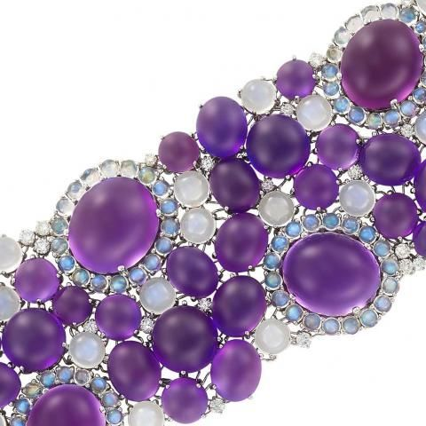 Wide 18k White Gold, cabochon Amethyst, Moonstone and Diamond Bracelet, the flexible cuff set with 52 oval and round cabochon Amethysts approximately 234.65 cts., embellished with 132 round cabochon Moonstones approximately 56.50 cts., accented by 114 round Diamonds approximately 4.65 cts., approximately 105 dwts. gross. Length 7 1/4 inches. Estimate: $12,000 - $18,000 | Doyle Auction House