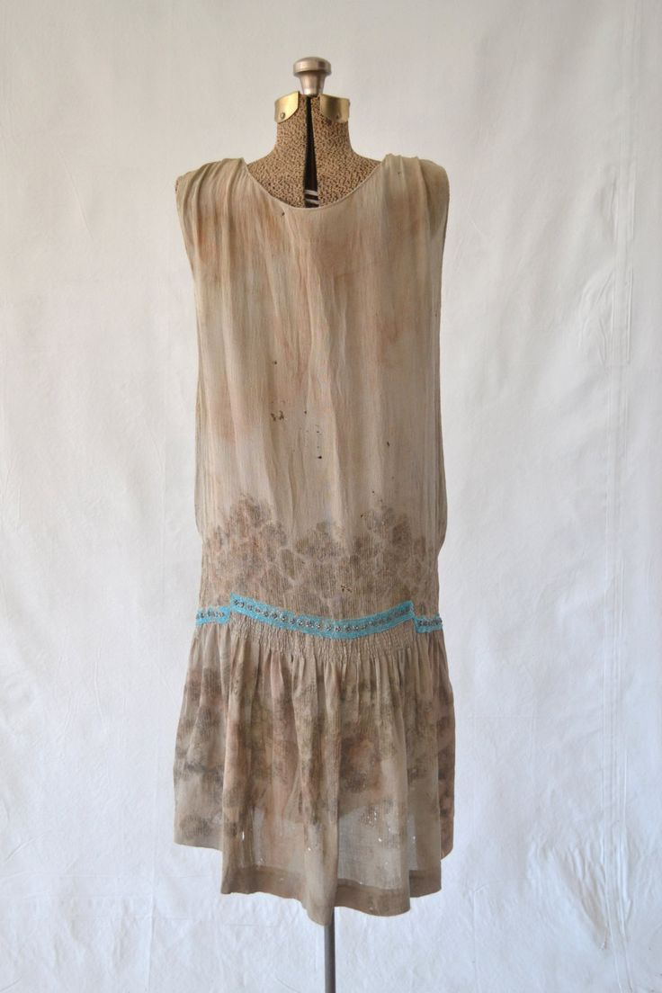 Sage green silk flapper dress circa 1920s. Exquisite turquoise and silver bead-work. An unusual piece although quite damaged with significant stains, small holes and missing bead-work. Not a wearable piece, sold as-is for design and historic purposes. Fits a womens size small.  MEASUREMENTS: (all are taken laying flat, meant to fit loosely)  length ~ 39 waist ~ 21 chest ~ 19.5 hips ~ 20