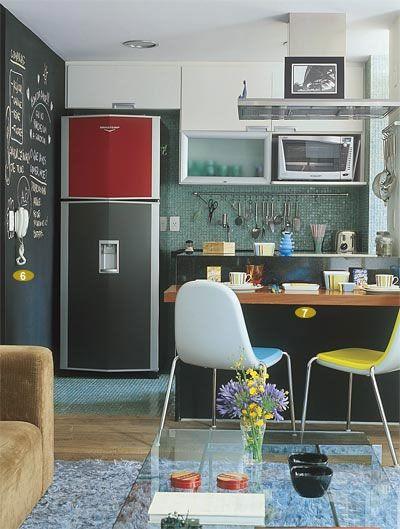 Apenas um balcão preto separa a sala da cozinha, neste apartamento de 68 m². Esta é a cor base da decoração, que ajuda na integração por estar nos dois ambientes. O casal de publicitários Fernando e Melissa Alves utilizaram detalhes coloridos para descontrair o espaço. Projeto dos arquitetos Ricardo Miura e Carla Yasuda.