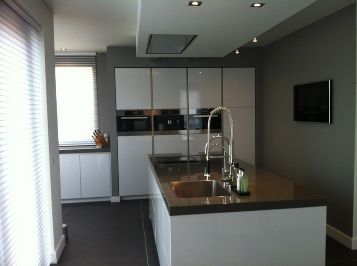 Hoogglans witte greeploze keuken met kook-/ spoeleiland en strakke kastenwand met verticale greeplijst — bij Eindhoven.