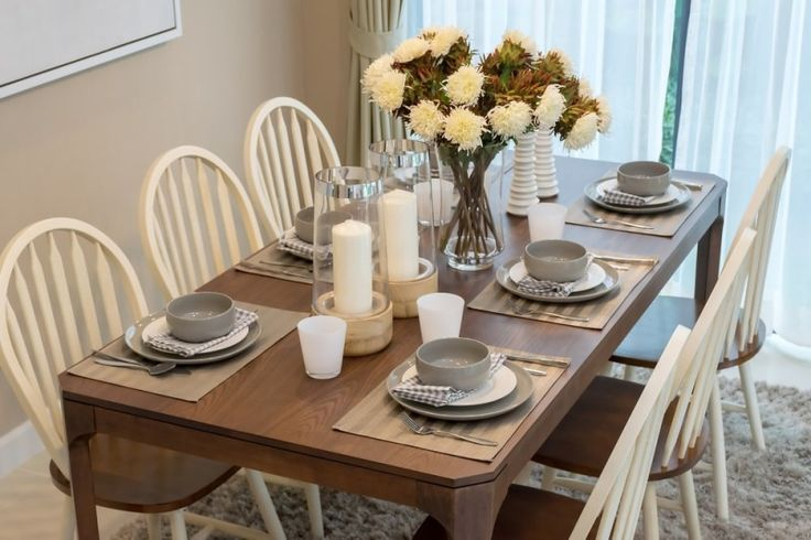 Modern dining room table with simple but stylish wooden chairs, a vase of flowers and an elegant table setting