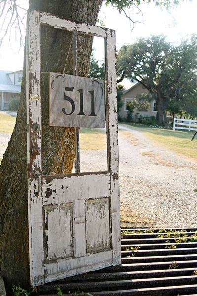Instead of just an address or welcome sign, try hanging something from an old door.