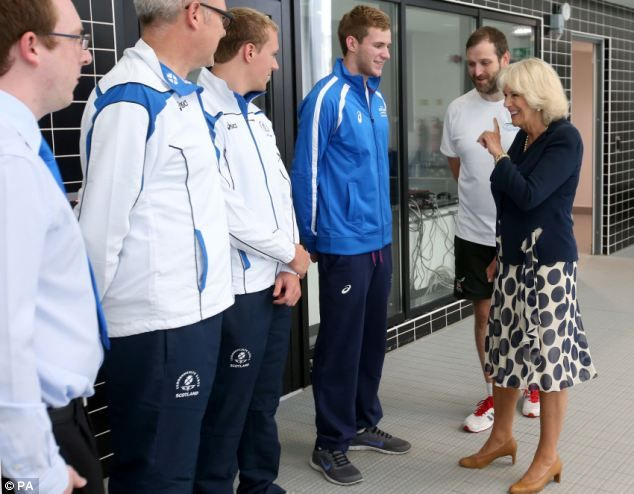 Camilla laughs with swimming coach Gordon Glass, Robbie Renwick (centre) and Jack Ness (blue top) ~~ meeting Team GB for the Commonwealth Games later this month in Glasgow Scotland. ~~ 9 July 2014