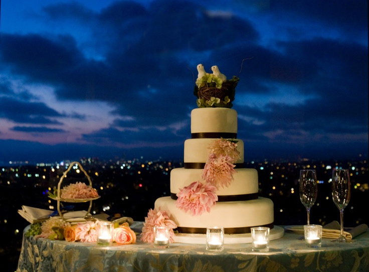 wedding cake at night with white frosting, brown ribbon, pink flowers and white doves on top