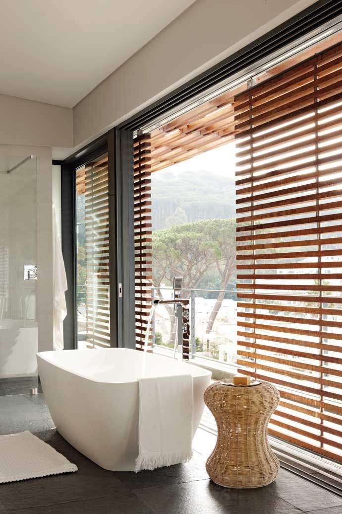 The tub in the main bathroom is perfectly positioned to make the most of the Cape Town mountain and tree views.