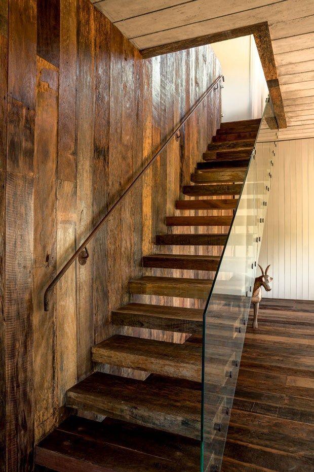 Лестница на второй этаж с ограждением из стекла, которое на скрывает деревянную стену, если смотреть из гостиной. .