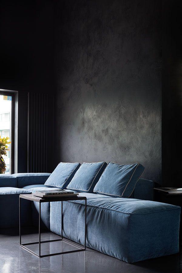 dark wall and a cozy blue velvet sofa