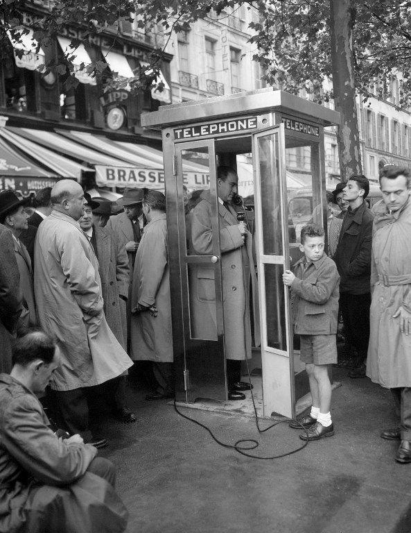 Un journaliste essaye une nouvelle cabine téléphonique installée en 1955 sur le boulevard Saint-Germain à Paris (AFP)