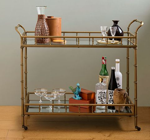 """Pier 1 Imports Made of: Wrought iron and glass From Pier 1 Imports, this37""""Wx14½""""Dx32¼""""H gold-toned bamboo bar cart is a mid-century classic. An antiqued finish gives it a vintage vibe. About $330; Pier 1 Imports"""
