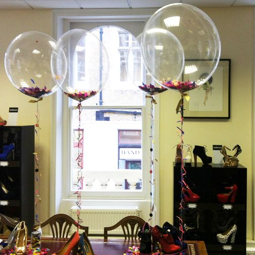 Centro de mesa decorado con globos transparentes rellenos de confeti.