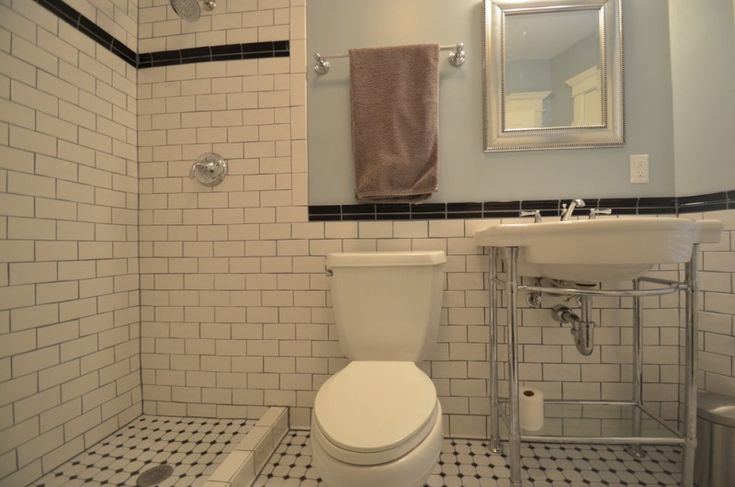 craftsman bathroom with white small tiles in flooring, white tiles in walls in the shower area, wainscoting in toilte and wastafel area, white toilet, white wastafel