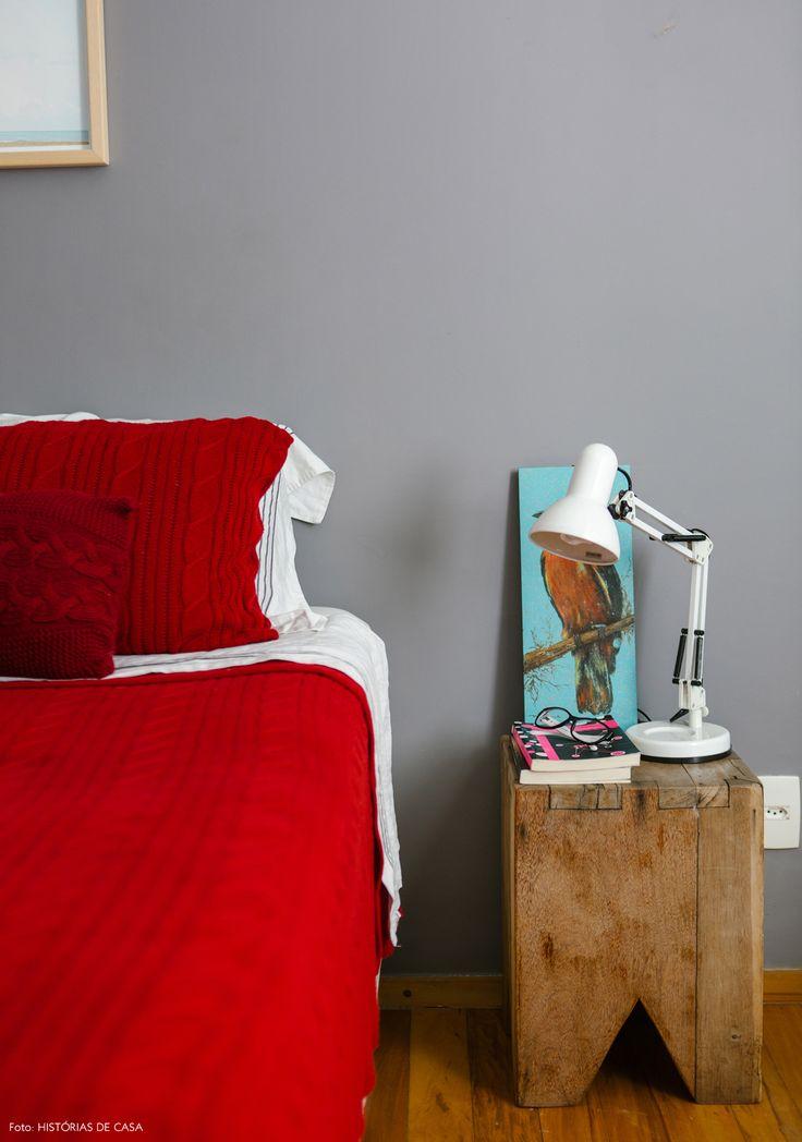 Quarto de casal tem parede pintada de cinza e roupa de cama de tricô na cor vermelha e banquinho de madeira usado como criado mudo.
