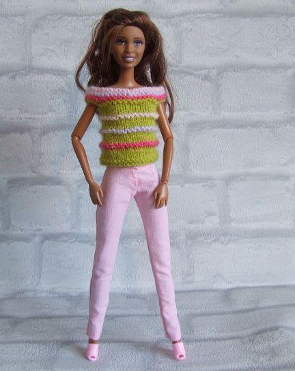 Gebreid truitje groen met roze ribbels op lichtroze strakke broek. Het truitje…