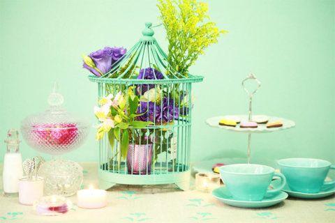 Um arranjo com flores artificiais dentro desta gaiola colorida.