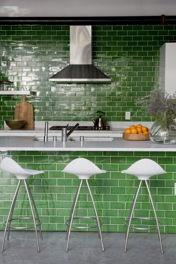 DiSC Interiors Gardein Industrial Kitchen * Chosen for visual impact and its reflective quality, Waterworks' Architectonics Tile in Clover Glossy covers a wall and island in the chef's kitchen. DISC Interiors offset the green with clean white elements, including tile grout, marble counters, and bar stools.