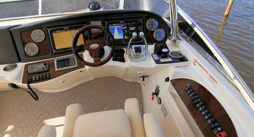 Meridian Yachts 441 Sedan: The starboard side helm wraps around the operator creating an efficient control station that is attractive in its functionality. Note the analog gauges to the outside of the hybrid touch screens.
