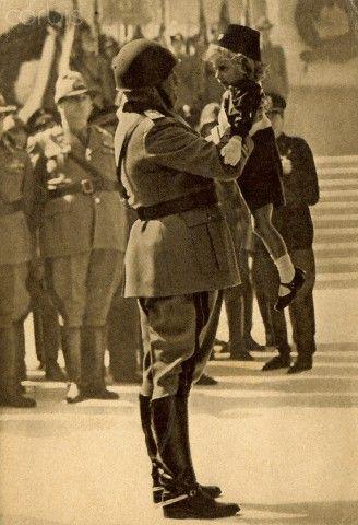 Mussolini con una niña vestida con el uniforme fascista en 1941.