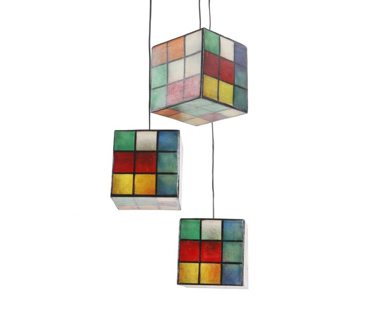 Lighting fixture in the shape of a cube, made out of fiberglass. It can be hung from the ceiling as the central lighting fixture of any space, or be put on any surface (table, shelf, floor) as a lamp standing on it own.  Dimensions: 20 x 20 cm Available in two colors: Color Rubik's and B&W Rubik's.  They come complete with an E14 bulb holder and you can use  as much wattage as you need.