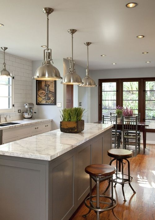 Traditional kitchen mixes with Industrial Chic..the lights, the white subway tiles and the white grey veined marble work tops..Love! Similar products can be found at Mandarin Stone www.mandarinstone.com